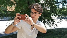 Young man taking photos with cell phone Royalty Free Stock Image