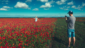 Young man taking photos on smartphone,  young girl running across field of red poppies, wanderlust tourism concept Stock Photography