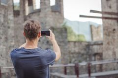 Young man is taking a picture of a castle stock image