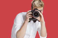 Young man taking picture with digital camera over red background Royalty Free Stock Photography