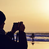 Young man taking a picture in front of the sea at dusk Royalty Free Stock Image