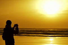 Young man taking a picture in front of the sea at dusk Royalty Free Stock Photography