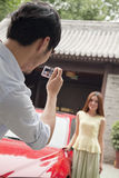 Young Man Taking a Picture of His Girlfriend and Car Stock Image