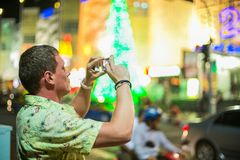 Young man taking picture on his mobile phone. Young man in green shirt taking picture on his mobile phone in the night time Royalty Free Stock Image