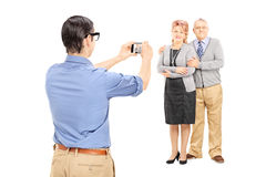 Young man taking picture of a mature couple. Young men taking picture of a mature couple isolated on white background Royalty Free Stock Photos