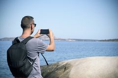 Young man taking a picture in Sardinia, Italy Stock Image