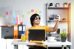Young Man Taking Picture While Working on Summer Vacation Season. At Office Stock Image
