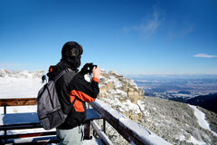 Young man taking pictures of a  beautiful winter mountain in Borovets,Bulgaria Stock Photo