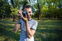 Young man taking pictures on retro camera Stock Image