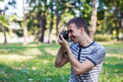 Young man taking pictures on retro camera Stock Photos