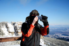 Young man taking pictures with a smartphone of a  beautiful winter mountain in Borovets,Bulgaria Royalty Free Stock Photos
