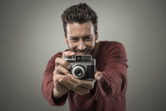 Young man taking pictures with a vintage camera Royalty Free Stock Images