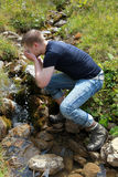 Young man taking a refreshment in the mountains Royalty Free Stock Photo