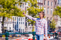 Young man taking self portrait in european city outdoors. Young adult holding smartphone camera to take a picture of Stock Images