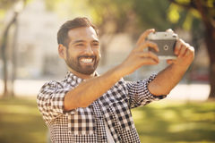 Young man taking a self portrait outdoors Royalty Free Stock Image