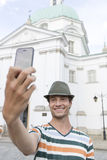 Young man taking self portrait outside St. Casimir Church, Warsaw, Poland Royalty Free Stock Images