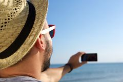 Young man taking a selfie with cell phone at the sea Royalty Free Stock Photography
