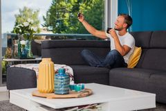 Young man taking a selfie while drinking coffee on the couch stock photography