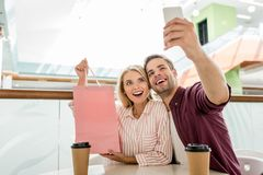 Young man taking selfie with girlfriend. Showing shopping bag at table with disposable cups of coffee in cafe royalty free stock photos
