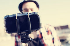 Young man taking a selfie with a monopod Royalty Free Stock Photography