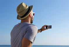 Young man taking selfie by the sea Royalty Free Stock Images
