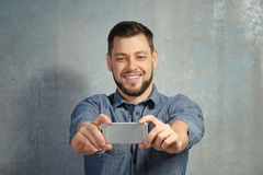 Young man taking selfie while standing near  wall. Young man taking selfie while standing near textured wall Stock Images