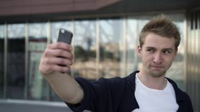 Young man taking a selfie in the street stock video footage