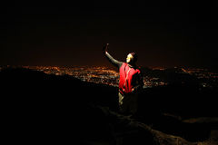Young man taking selfie on top of the hill observing the night city view. Stock Image