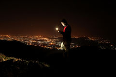 Young man taking selfie on top of the hill observing the night city view. Stock Photography