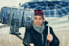 Young man taking a selfie under the rain Royalty Free Stock Photography
