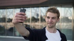 Young man taking selfies with different expressions stock video footage
