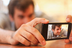 Young man taking selfportrait on cell phone Royalty Free Stock Photo