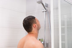 Young man taking a shower in the bathroom. Young man taking a shower, standing under flowing water in shower cabin with transparent glass doors in the bathroom Stock Photos