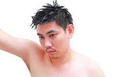 Young man taking a shower and standing under flowing water in bathroom. 