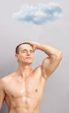 Young man taking shower under a raining cloud Royalty Free Stock Image