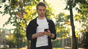 Young man taking smartphone from pocket and texting