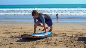 Young man taking a surfing training on a beach.  stock footage