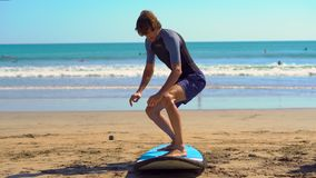 Young man taking a surfing training on a beach.  stock video footage