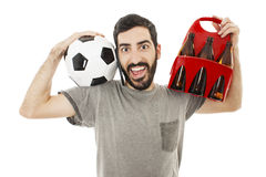 Young man talk on mobile phone happy and excited, holding ball and pack of beer Royalty Free Stock Photo