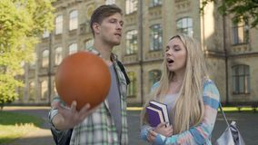 Young man talking with beautiful blonde near college, trying to impress girl. Stock footage stock footage