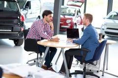 Young man talking with car dealer. Young men talking with car dealer, listens benefits in buying Stock Photos