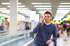 Young man talking by cell phone at airport waiting Royalty Free Stock Photography