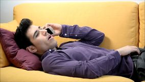 Young man talking on cell phone laying on couch stock video footage