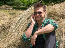 Young man talking on a cell phone while sitting in haystacks Royalty Free Stock Photos