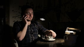 Young man talking on cellphone in cafe at night stock footage