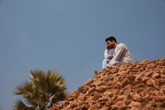 Young man talking with a cellphone sitting in a place. A man talking over a cellphone sitting on a high concrete structure unique royalty free image stock image