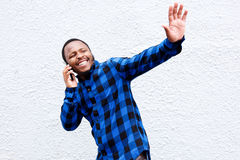 Young man talking on cellphone and waving hand Royalty Free Stock Photos