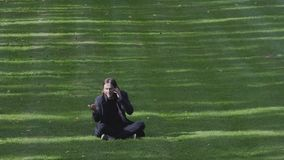 Young Man Talking Happily On Cell Phone In The Park. Young Adult Male Sitting On The Grass With His Cell Phone Talking Joyful, Enjoying A Sunny Early Autumn stock video footage