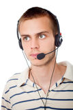 Young man talking on headset. Against a white background Stock Photo