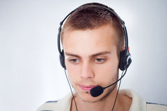Young man talking on headset. And looking down Royalty Free Stock Photography